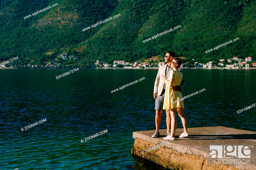 Stock Photo: A couple in love stands hugging on a pier in the Bay of Kotor near Perast against the backdrop of green slopes . High quality photo.