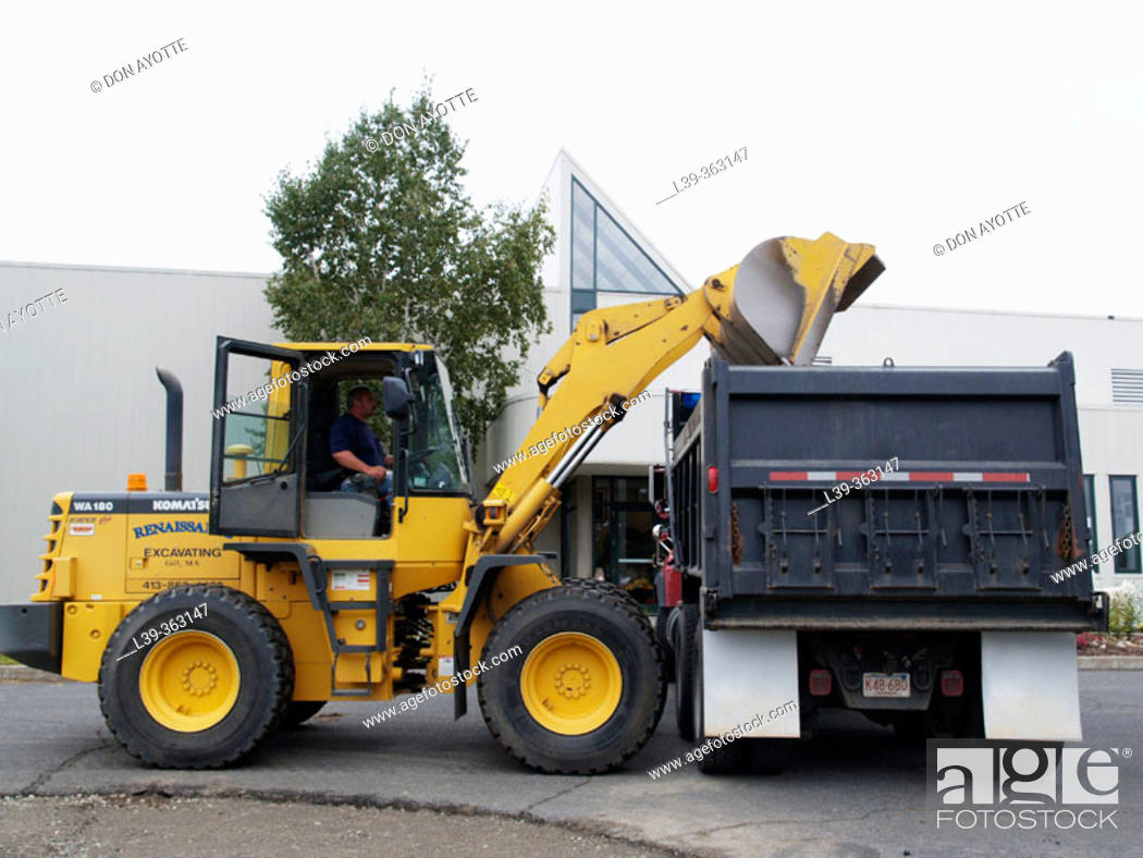 Stock Photo: Dump truck and front end loader removing asphalt in Turners Falls, Massachusetts. USA.