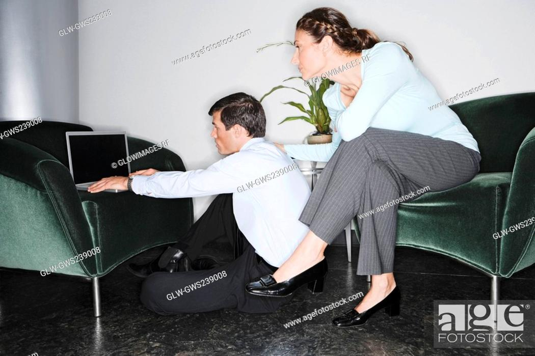 Stock Photo: Businessman using a laptop with a businesswoman sitting behind him.