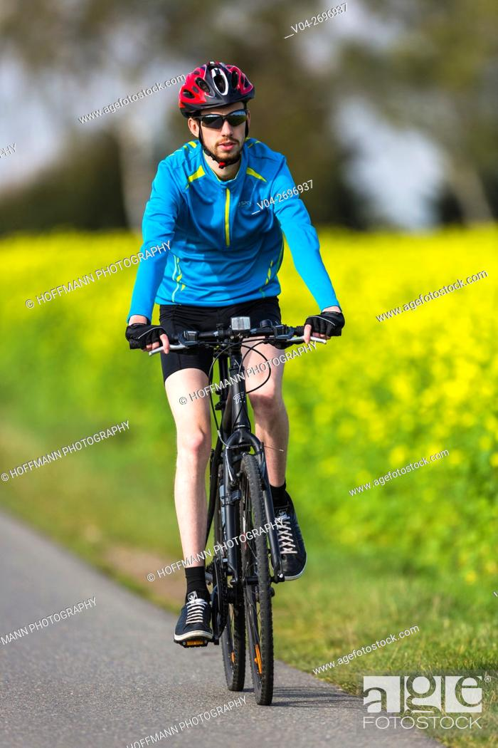 Imagen: Young man riding his bike in the countryside, Lower Saxony, Germany, Europe.