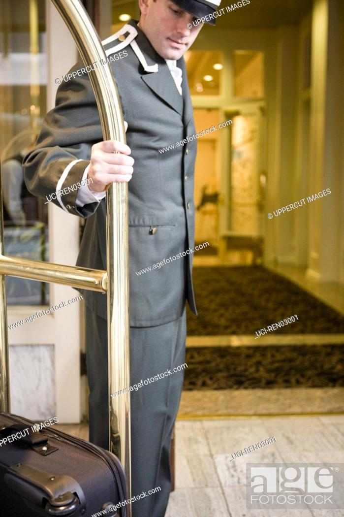 Stock Photo: Bellhop pulling luggage cart.
