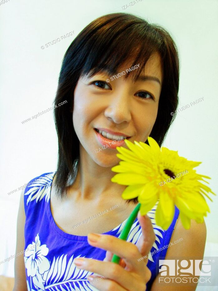 Imagen: Portrait of a mid adult woman holding a Gerbera Daisy flower and smiling.