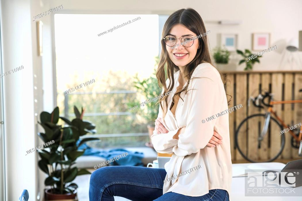 Stock Photo: Portrait of smiling young woman sitting on table at home.