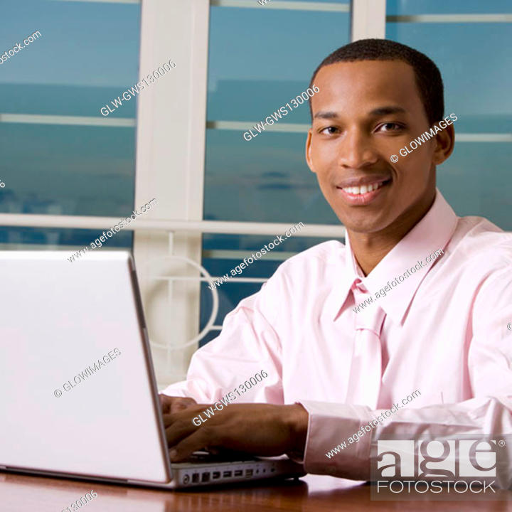 Stock Photo: Portrait of a businessman using a laptop.