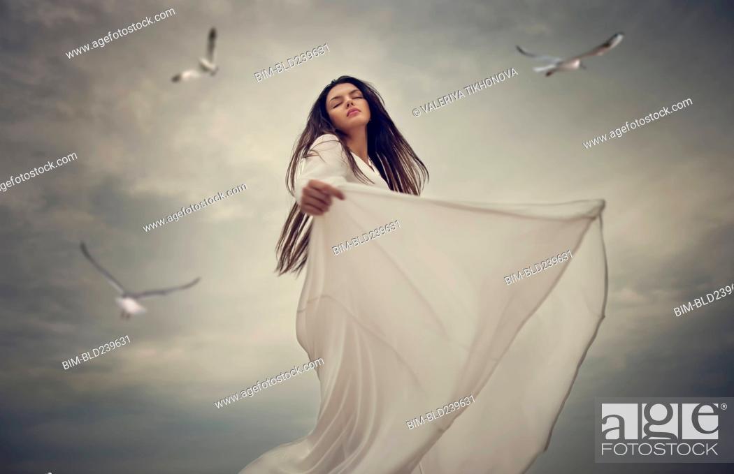 Stock Photo: Birds flying near dancing Caucasian woman.