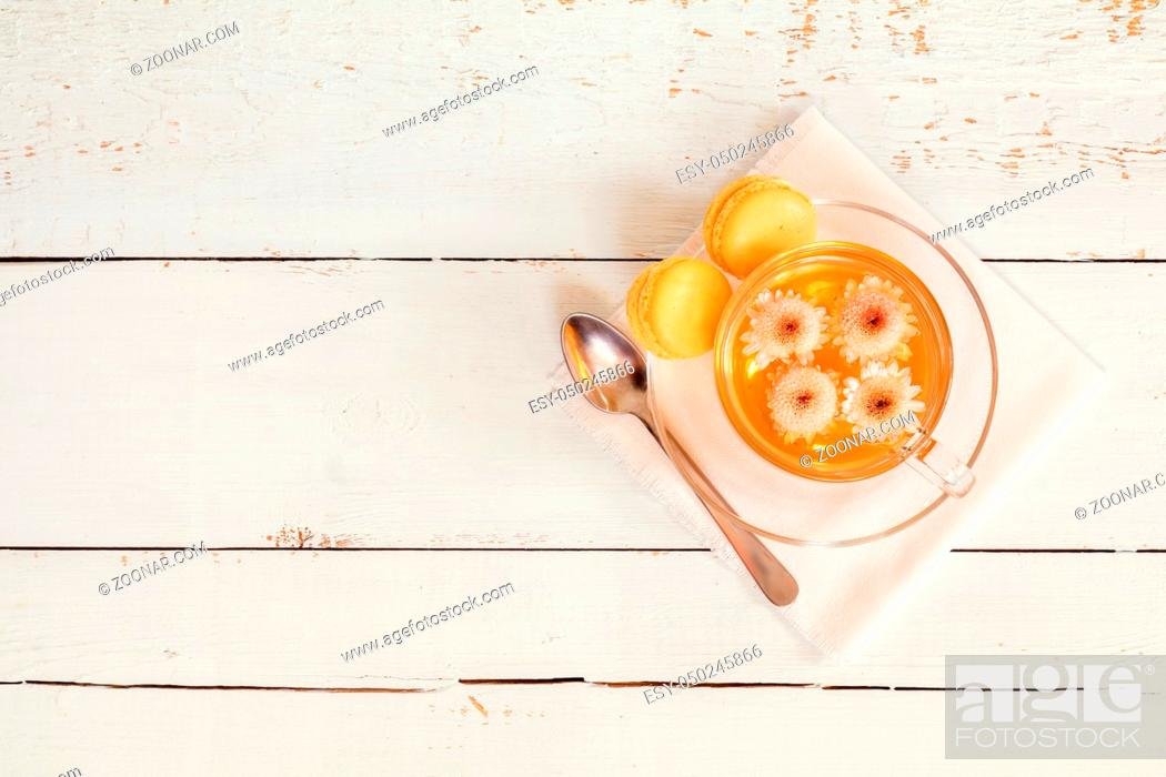 Stock Photo: Cup of tea with chrysanthemum flowers and macaroons on the light wooden table. Top view. Coloring and processing photo.