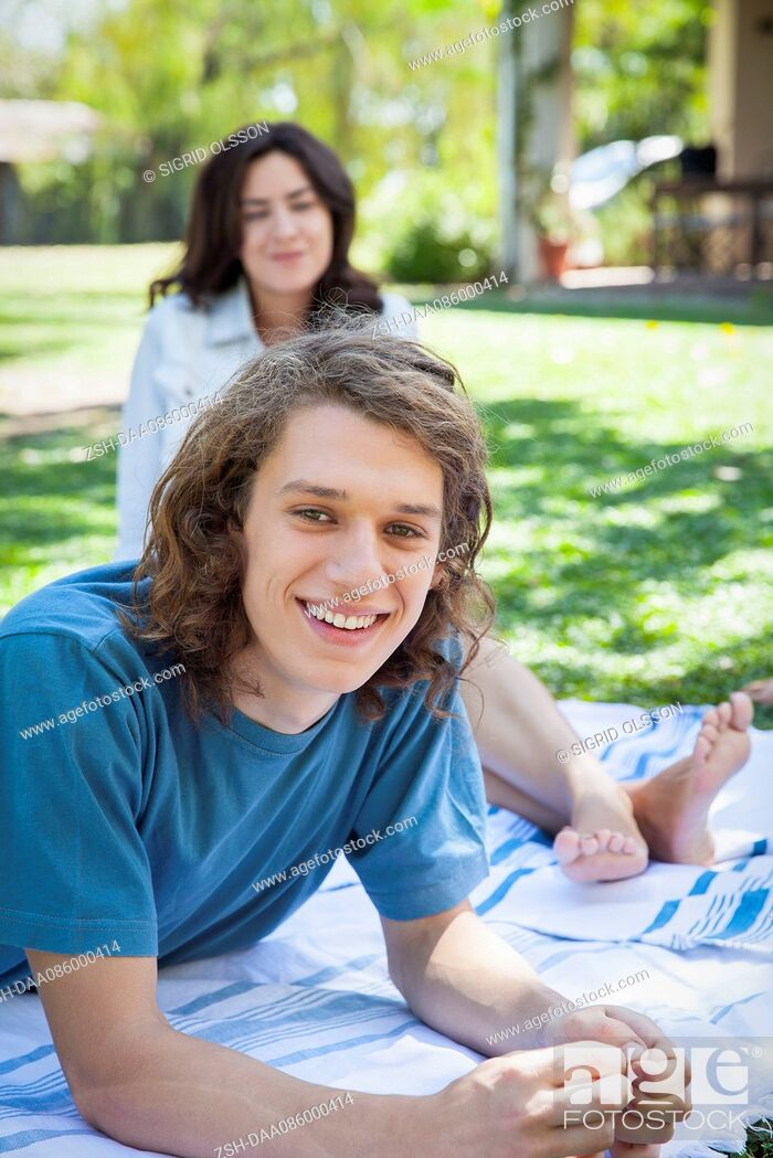 Stock Photo: Man relaxing on picnic blanket with friend.