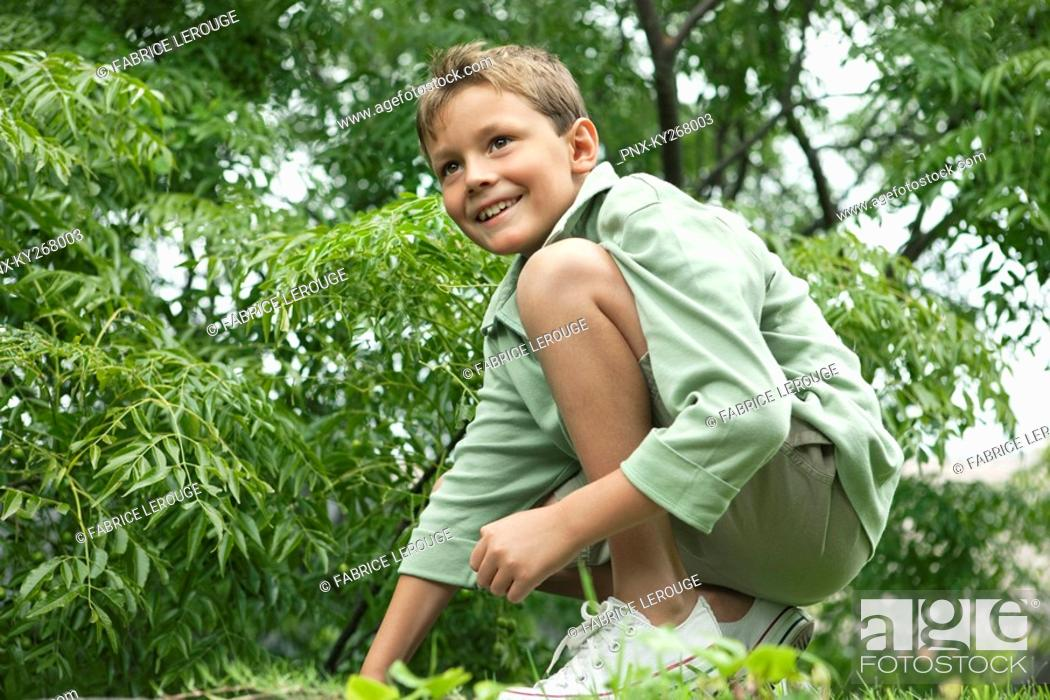 Stock Photo: Boy playing in a garden and smiling.