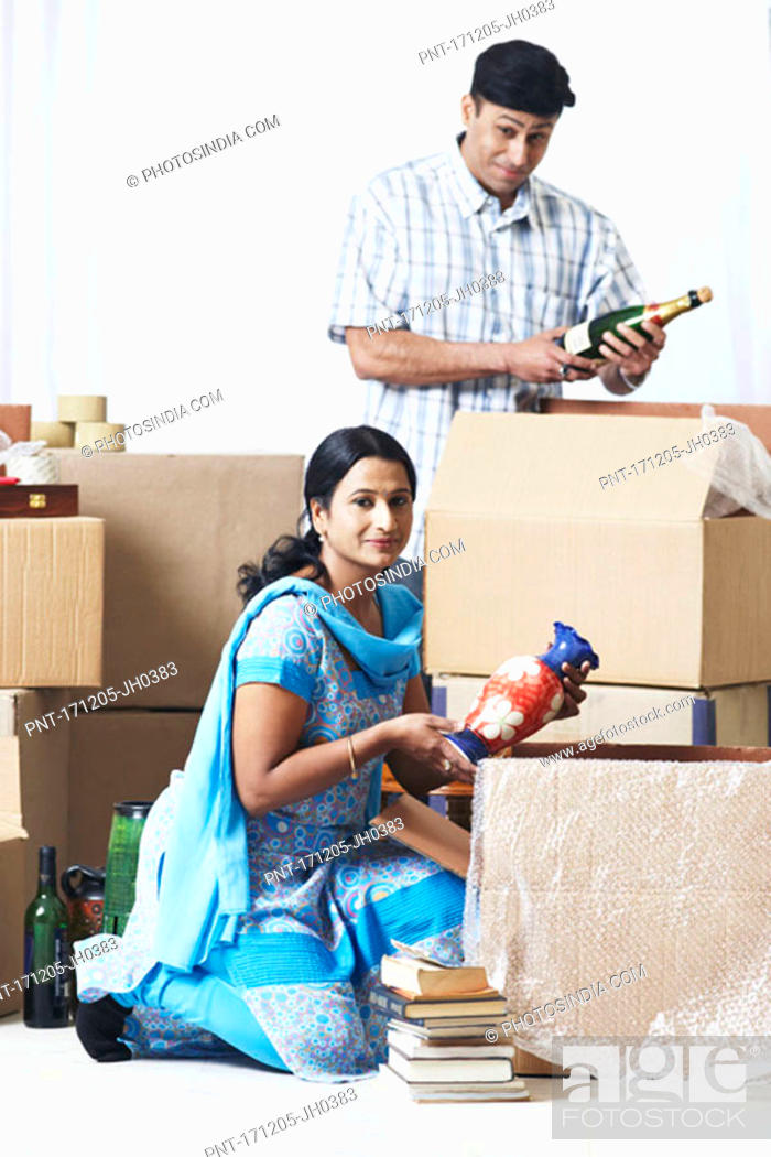 Stock Photo: Mid adult couple unpacking cardboard boxes.