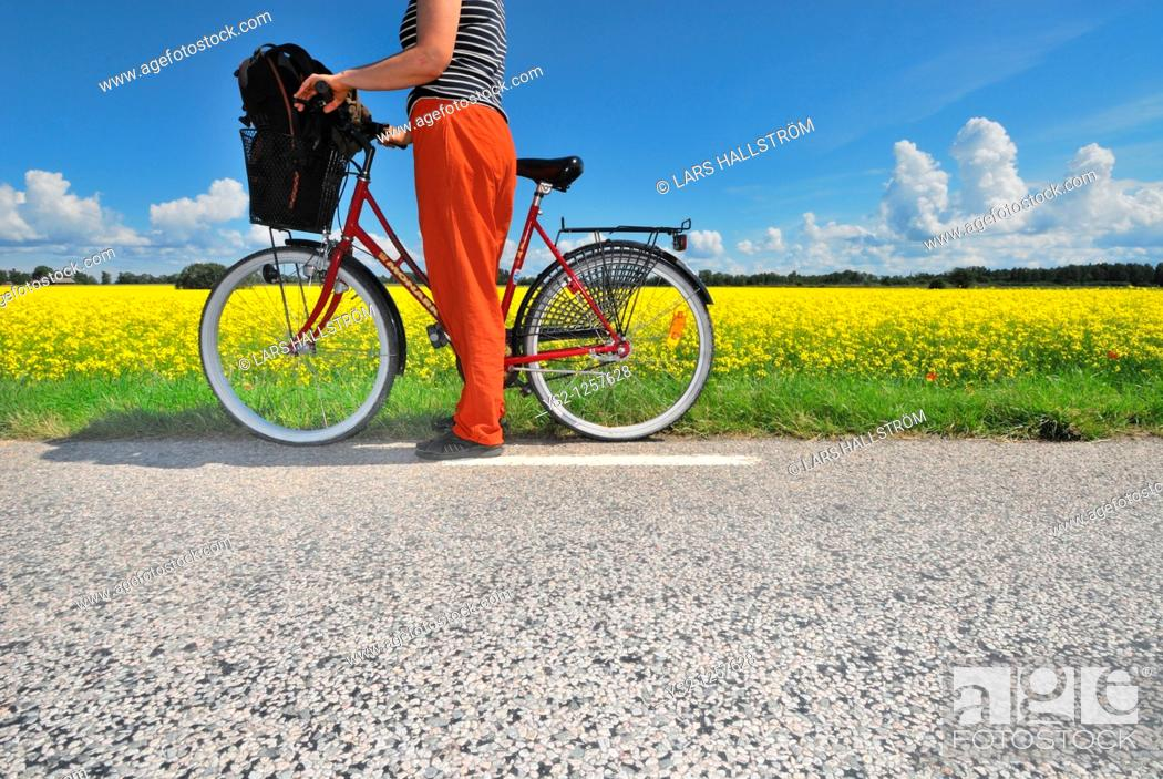 Stock Photo: Woman with bicycle watching landscape, Östergötland, Sweden.