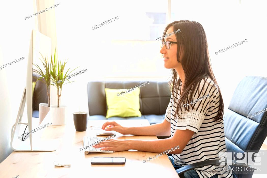 Stock Photo: Woman at desk working on computer.