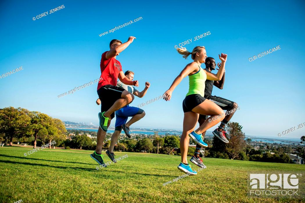 Stock Photo: Group of young adults training in field.