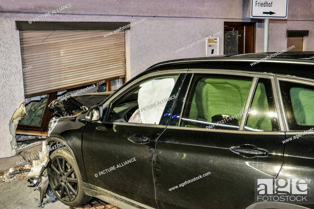 Stock Photo: 11 December 2019, Baden-Wuerttemberg, Gerlingen: A car with a destroyed bonnet stands in front of a partially smashed living room wall of a detached house.