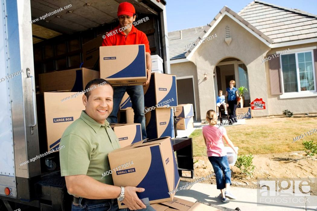 Stock Photo: Family unloading removal van in front of house.