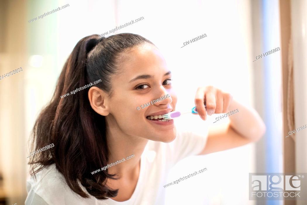 Stock Photo: Portrait confident woman brushing teeth.