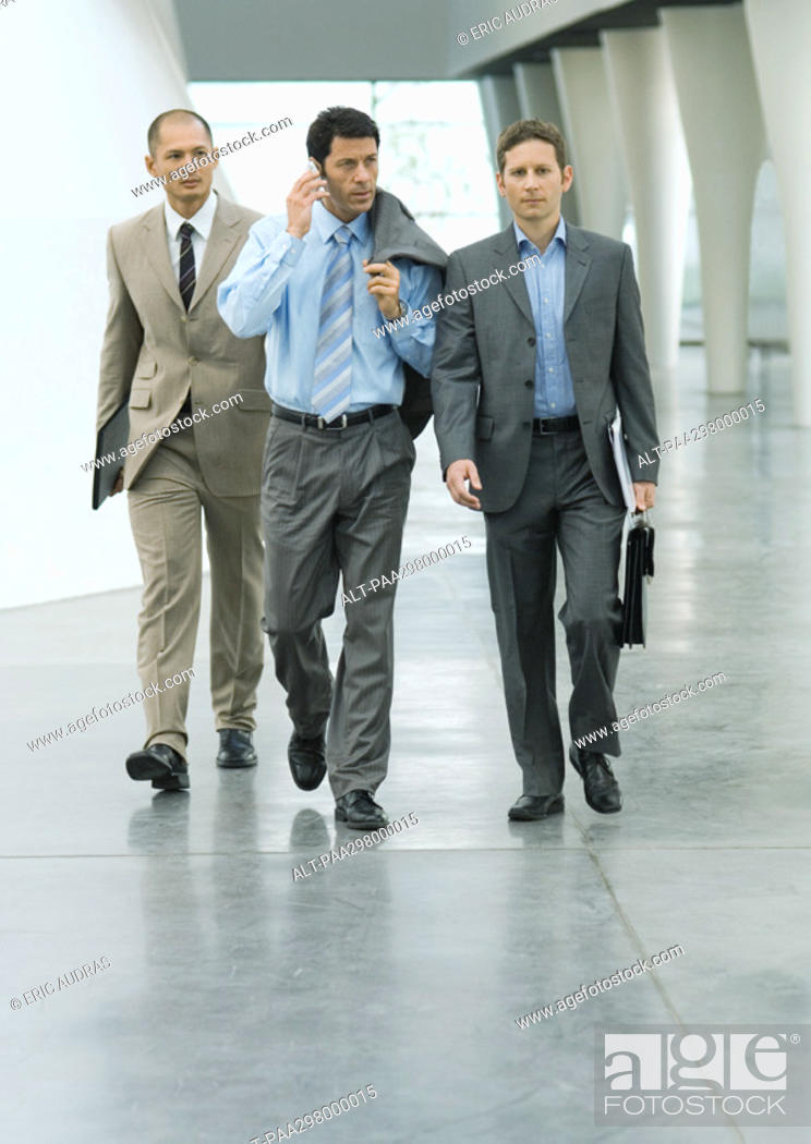 Stock Photo: Three businessmen walking through lobby, one using cell phone.