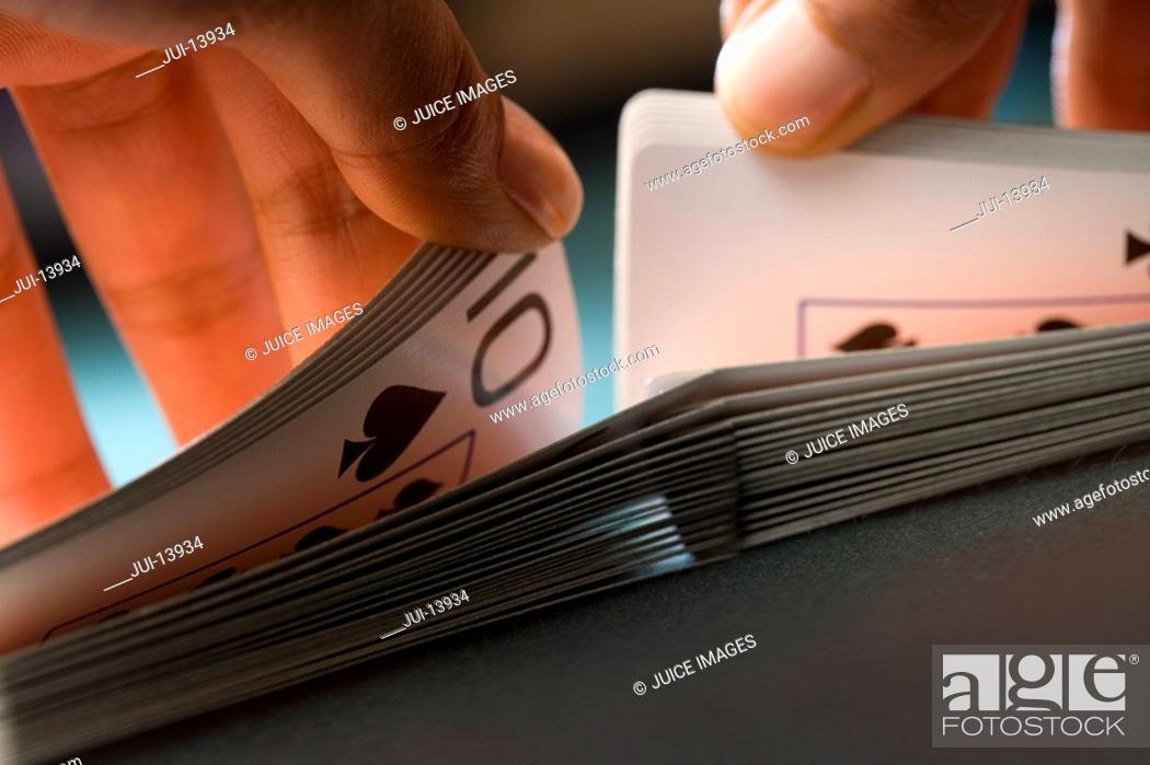 Stock Photo: Close up of mans hands shuffling playing cards.