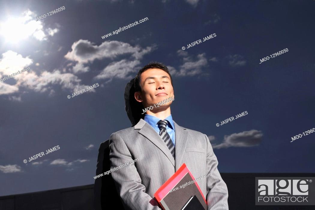 Stock Photo: Smiling Businessman leaning against reflective wall outside eyes closed holding notebook.