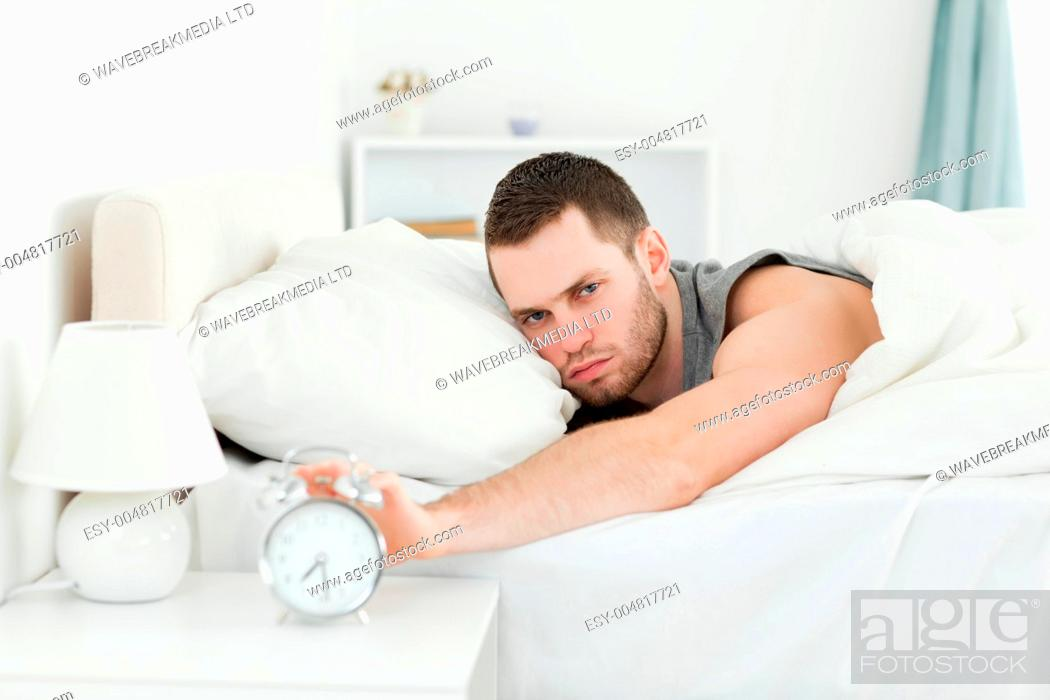 Stock Photo: Tired young man switching off his alarm clock.