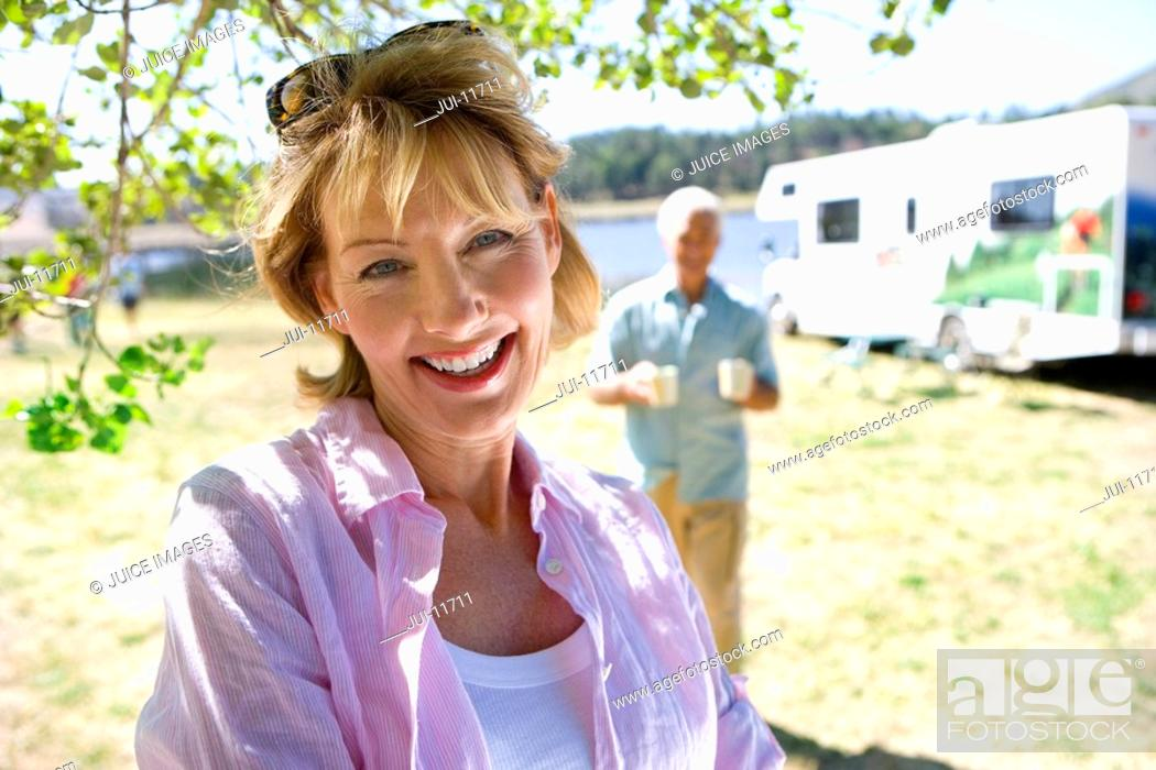 Stock Photo: Mature woman by husband and motor home outdoors, smiling, portrait, close-up.