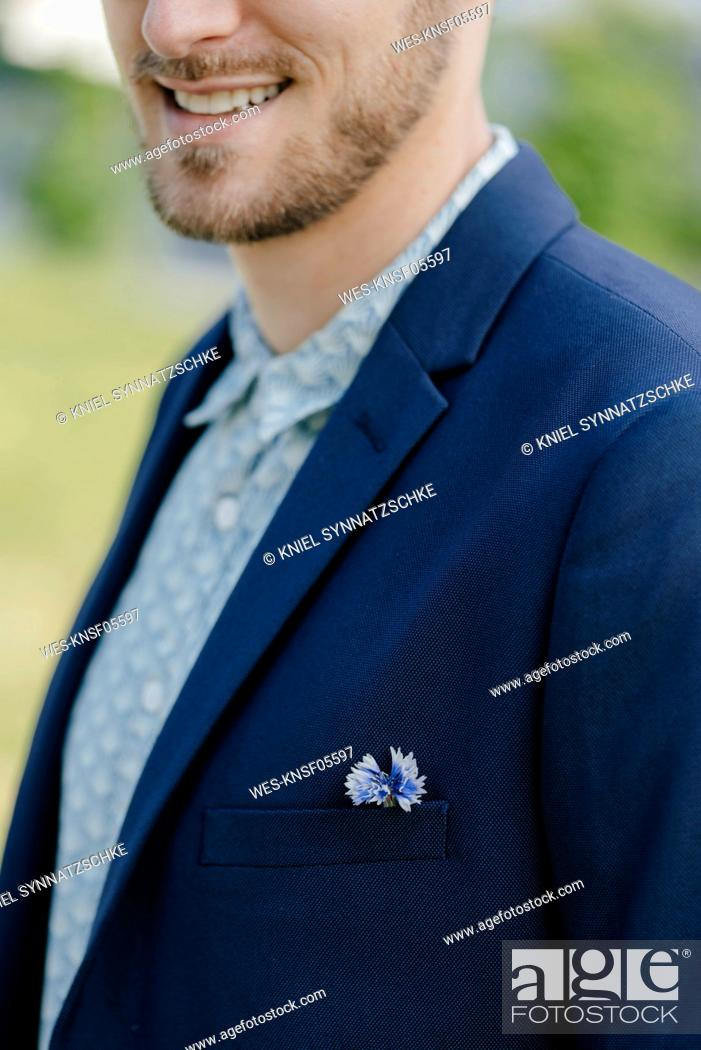 Stock Photo: Flower in young businessman's jacket pocket, close up.