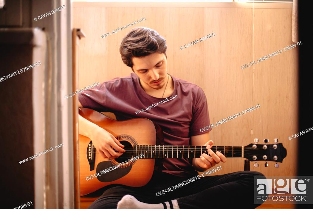 Imagen: Young man playing guitar while sitting on balcony floor at home.