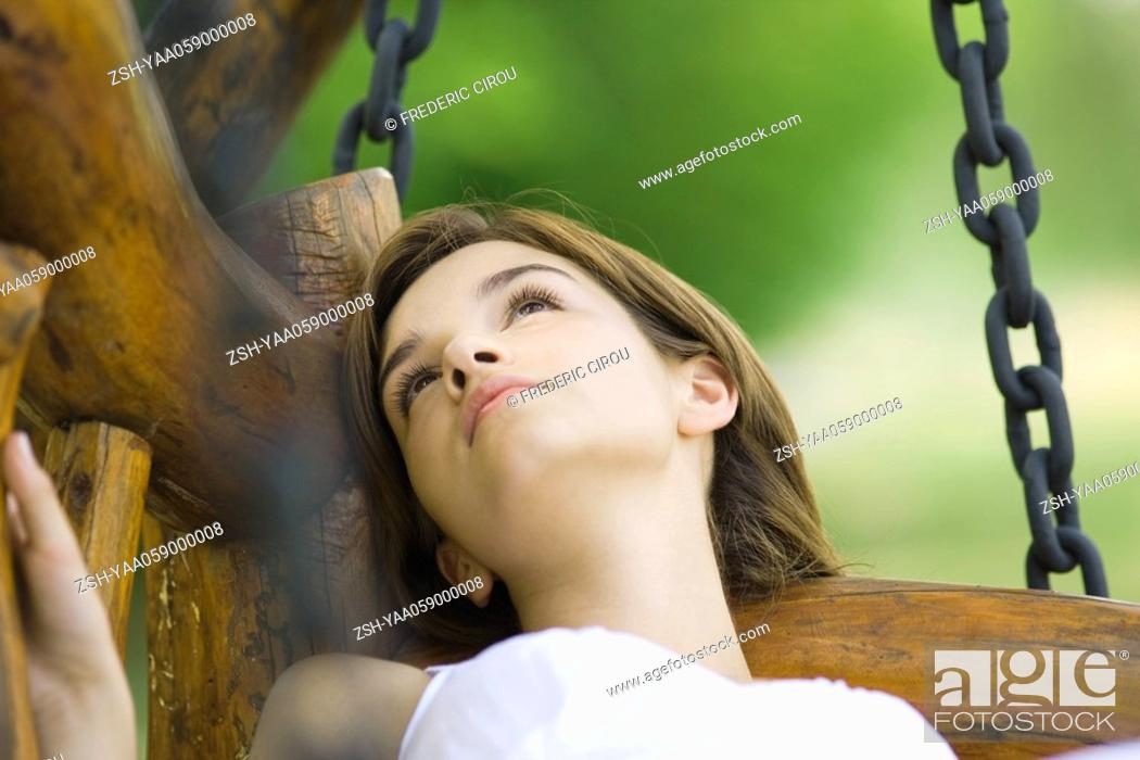 Stock Photo: Young woman lying on swing, close-up.