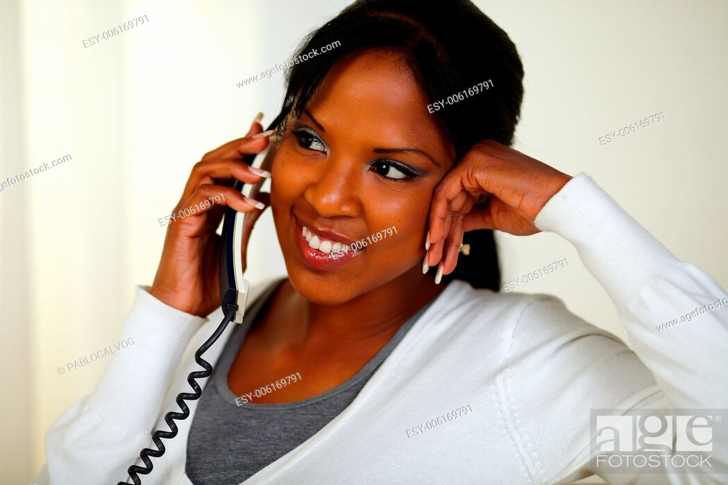 Stock Photo: Portrait of a charming relaxed woman speaking on phone at soft colors composition.