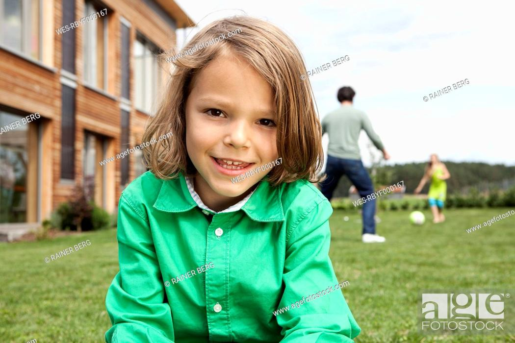 Stock Photo: Germany, Bavaria, Nuremberg, Boy smiling, portrait, father and daughter playing in background.
