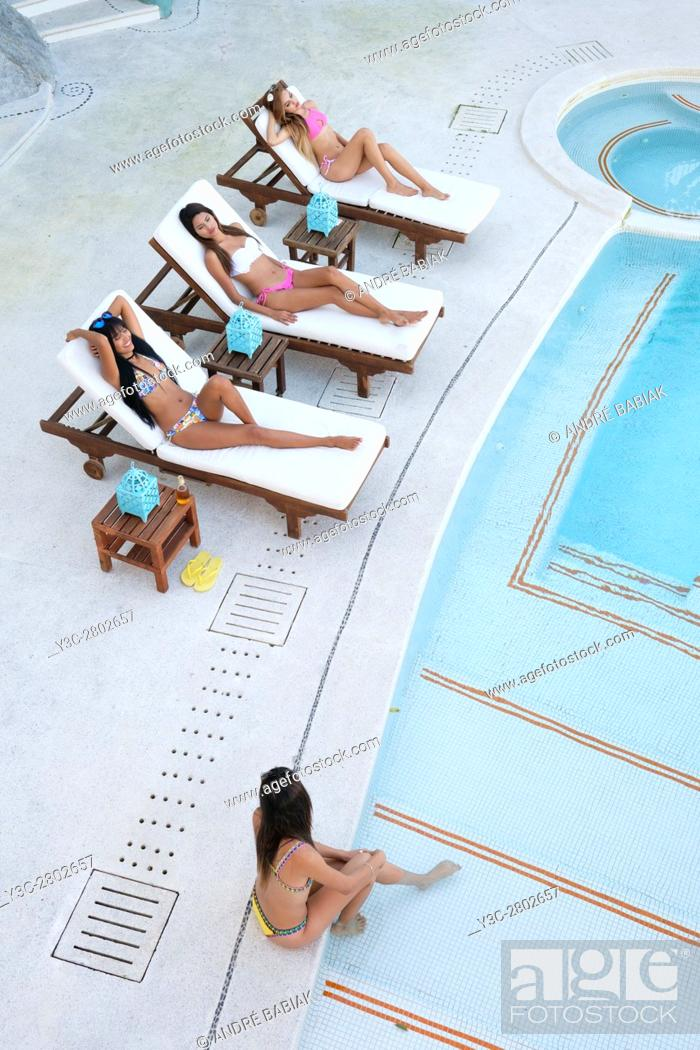 Stock Photo: Four young women tanning and enjoying day at swimming pool.