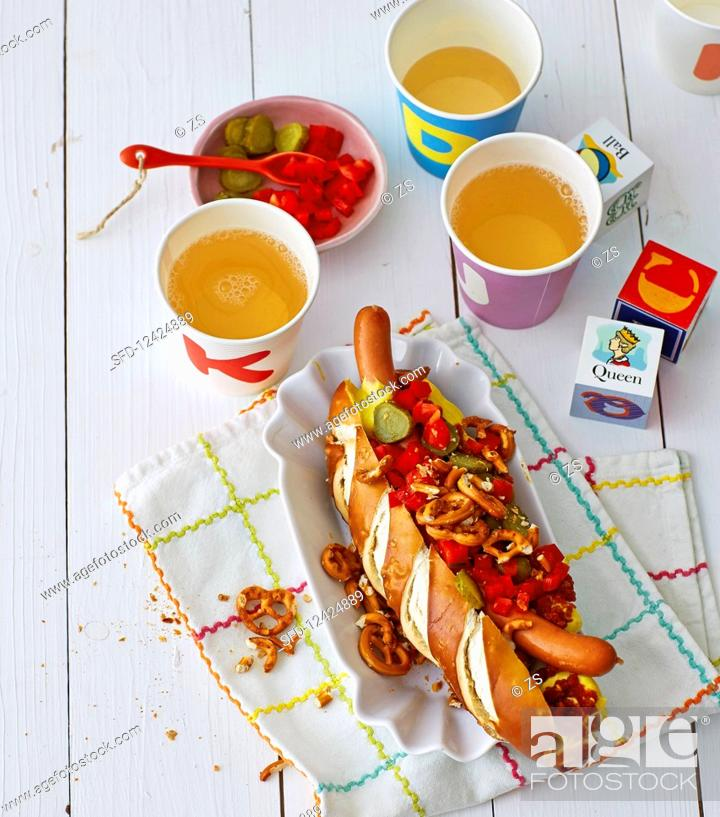 Stock Photo: A hot dog in a lye bread roll with mini pretzels.