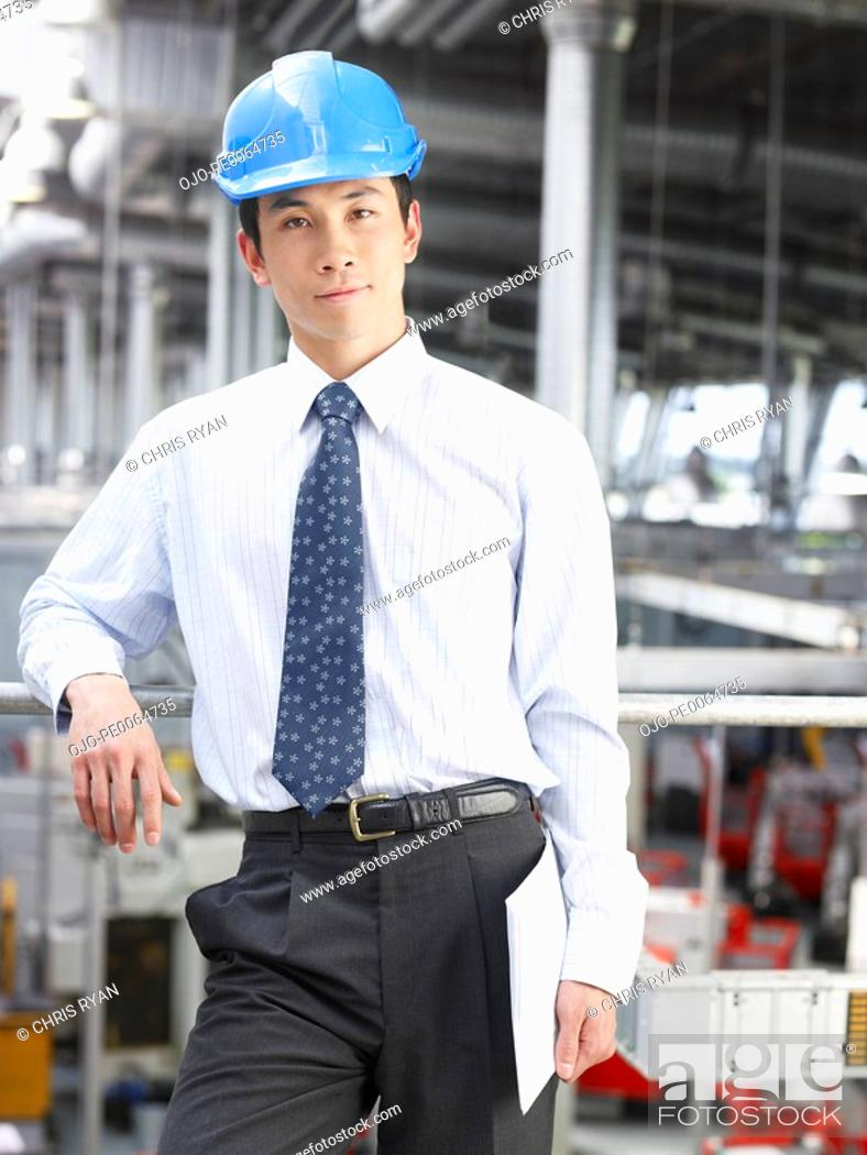 Stock Photo: Businessman wearing hard-hat in warehouse.