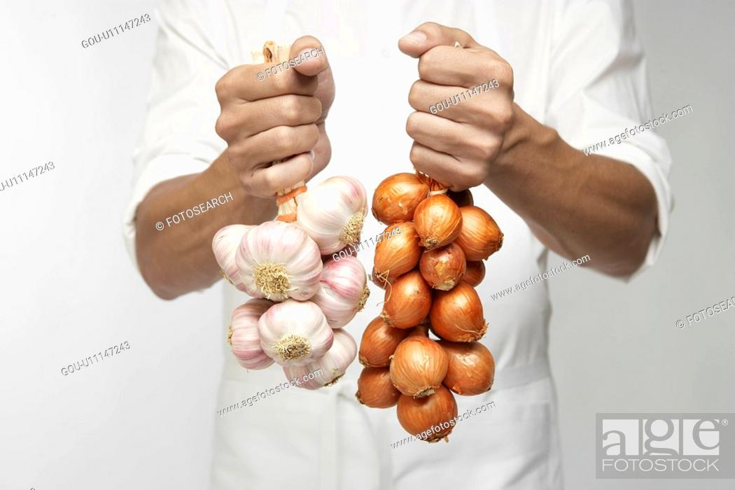 Stock Photo: Chef holding bunch of garlic and shallot onions (mid section).