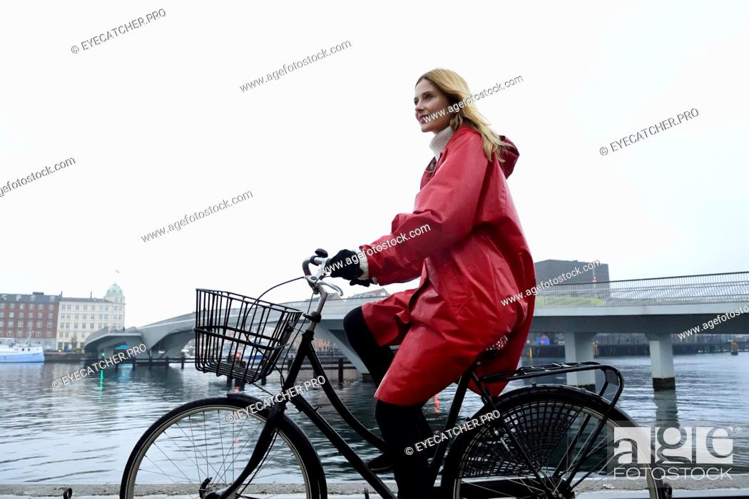 Stock Photo: Denmark, Copenhagen, woman riding bicycle at the waterfront in rainy weather.