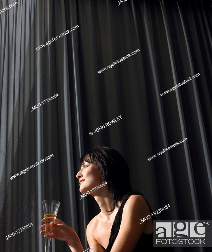 Stock Photo: Woman holding champagne in front of curtains indoors.