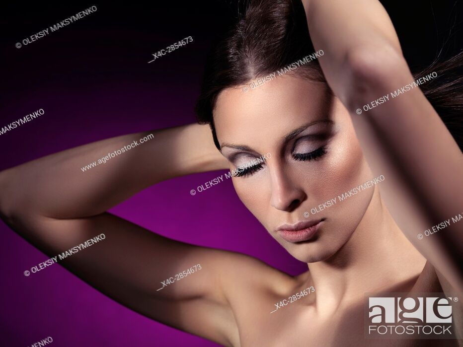 Stock Photo: Beauty portrait of a young woman with closed eyes and artistic makeup and long eyelashes on purple background.