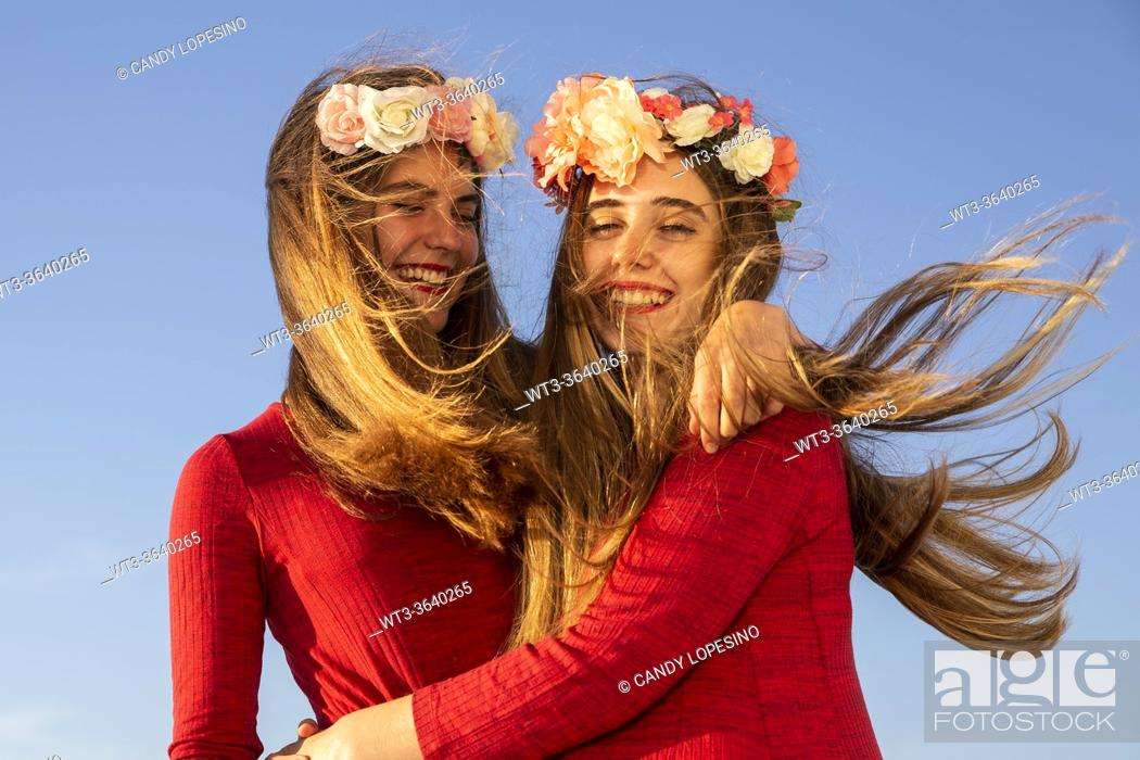 Stock Photo: Two young girls with red dress and long blonde hair at the wind and roses having fun.