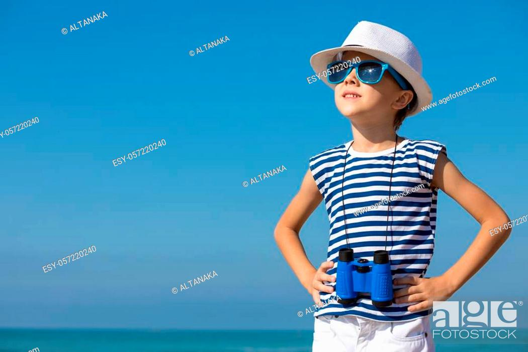 Stock Photo: One happy little boy playing on the beach at the day time. He are dressed in sailor's vest. Kid having fun outdoors. Concept of sailor on vacation.