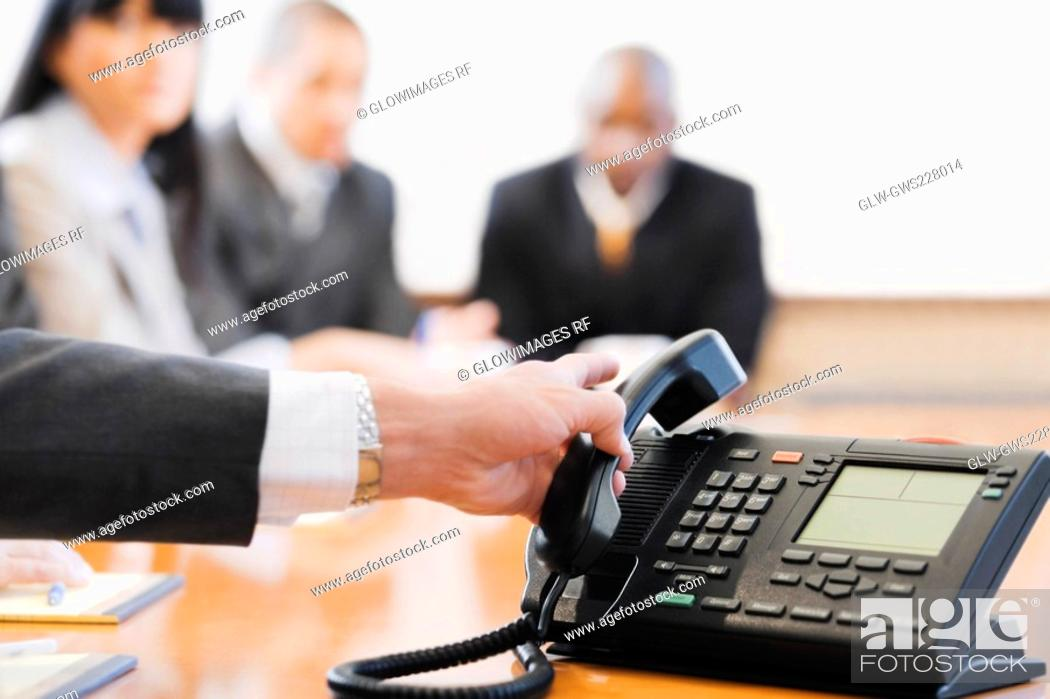 Stock Photo: Close-up of a businessman's hand holding a conference phone receiver.
