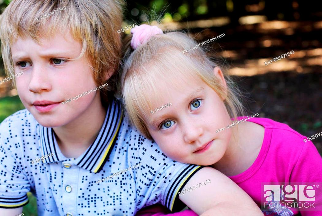 Stock Photo: Portrait of happy 5 years old girl with her autistic 8 years old brother outdoors.