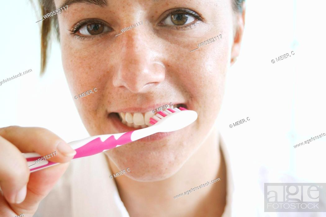 Imagen: Young woman brushes her teeth.