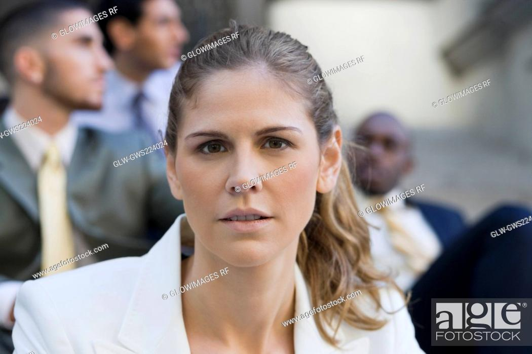 Stock Photo: Close-up of a businesswoman smiling with three businessmen in the background.