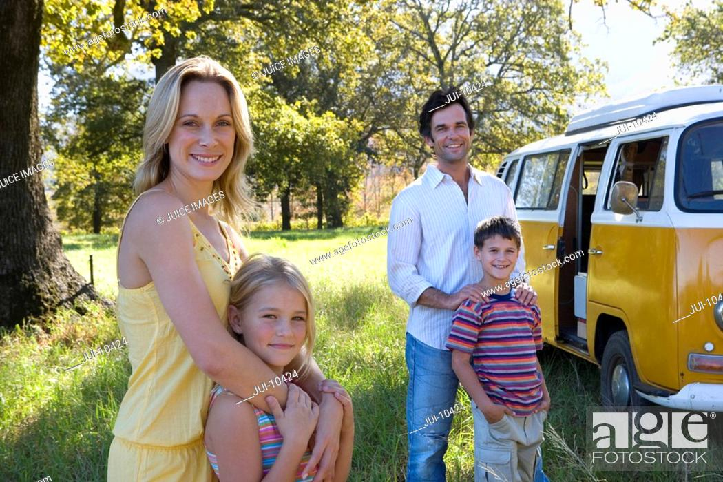 Stock Photo: Mother embracing daughter 5-7 by father embracing son 6-8 in field by camper van, smiling, portrait.