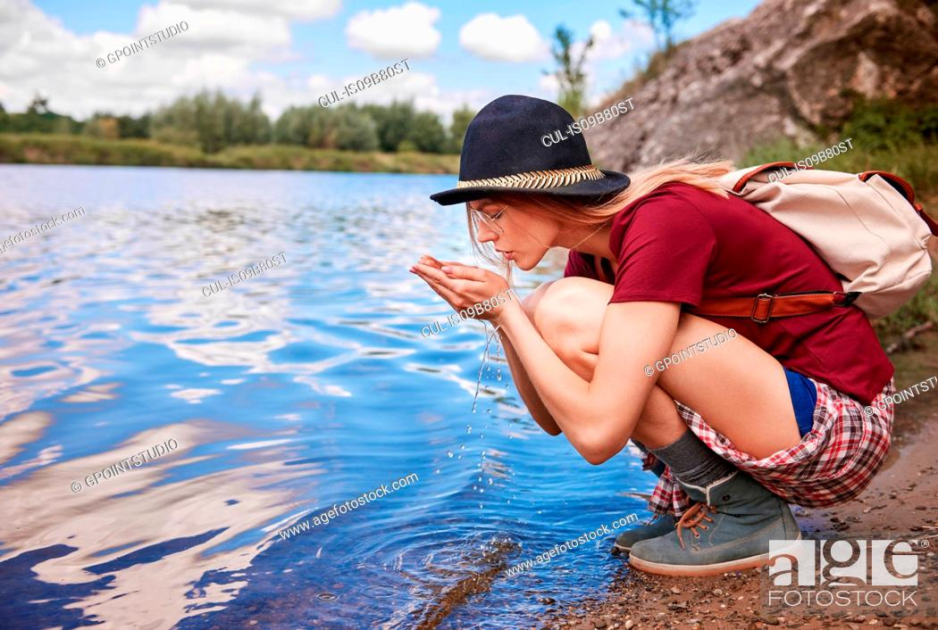 Stock Photo: Woman crouching by waters edge scooping up water in hands, Krakow, Malopolskie, Poland, Europe.