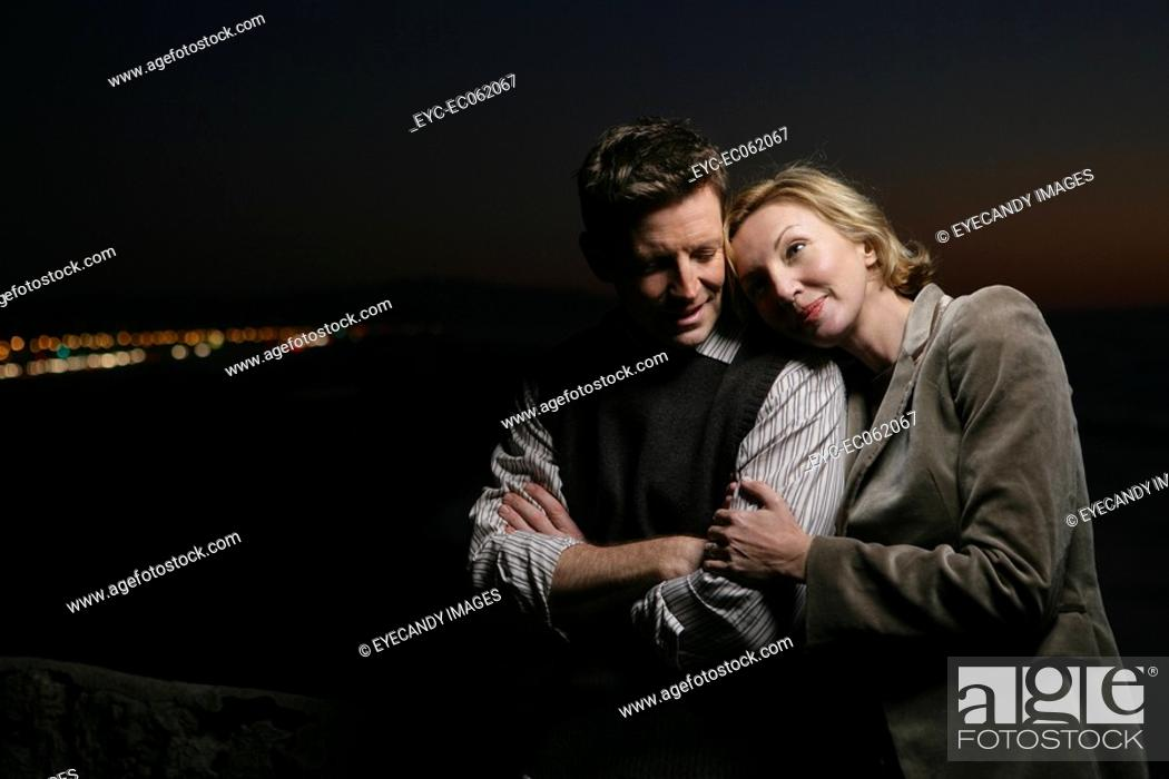 Stock Photo: Mature couple embracing at night.