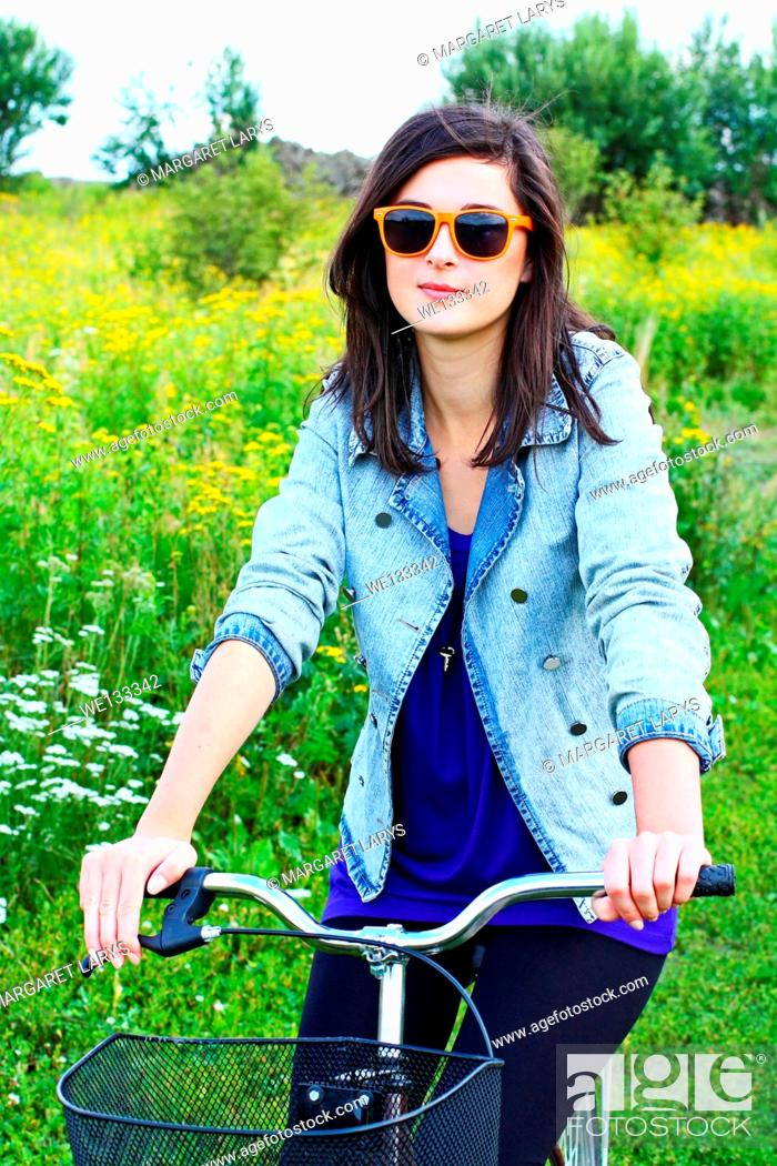Stock Photo: Beautiful young woman and a bike in summer fields Beautiful young woman and a bike in the summer fields with wildflowers on a sunny summer day.