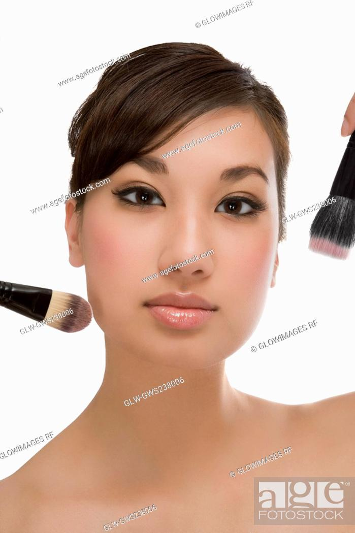 Stock Photo: Close-up of a young woman holding make-up brushes and applying make-up.