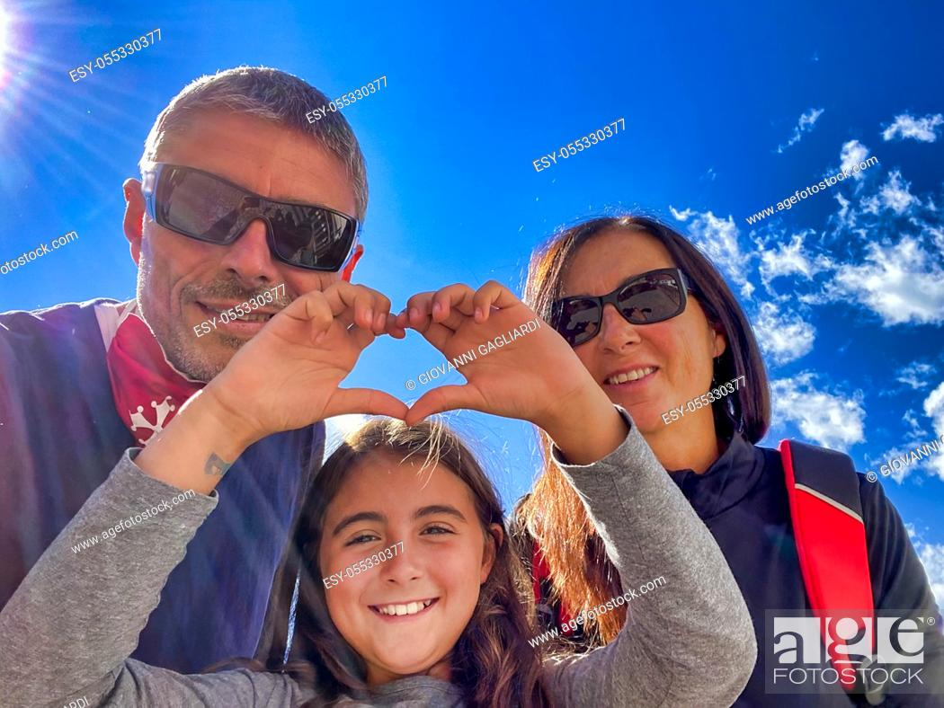 Stock Photo: Family of three people on a mountain trail with young girl making heart sign. Holiday concept.
