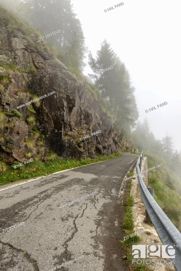 Stock Photo: guardrail on steep slope at Vivione pass narrow mountain road, shot in cloudy summer light in Scalve valley, Bergamo, Orobie, Lombardy, Italy .