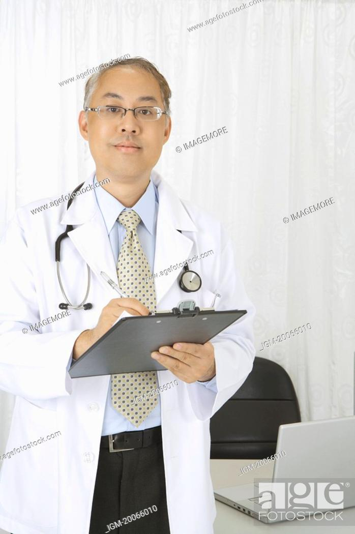 Stock Photo: Doctor writing on clipboard and looking at the camera.